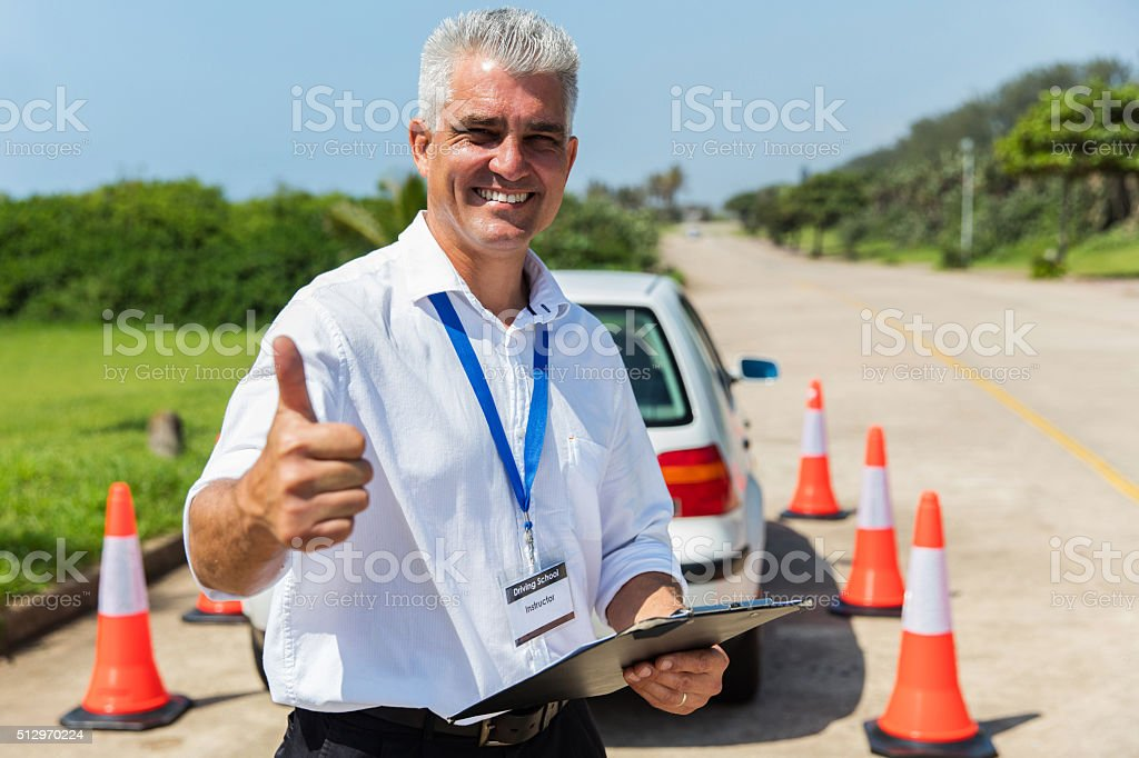 driving school instructor thumb up stock photo