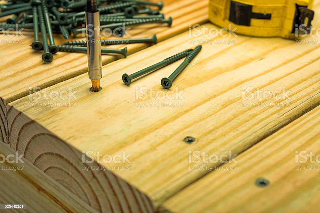 Driving screws into a PT Deck Board stock photo
