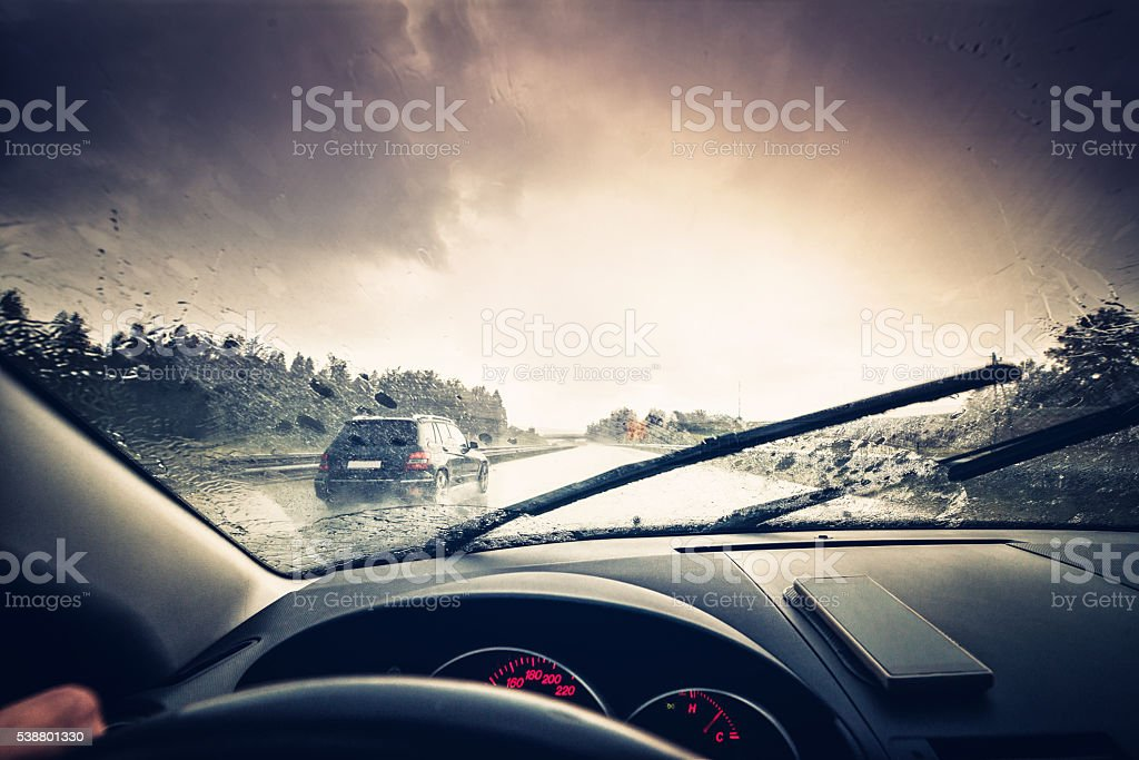 A car driving through a rainy highway with the windshield wipers in...