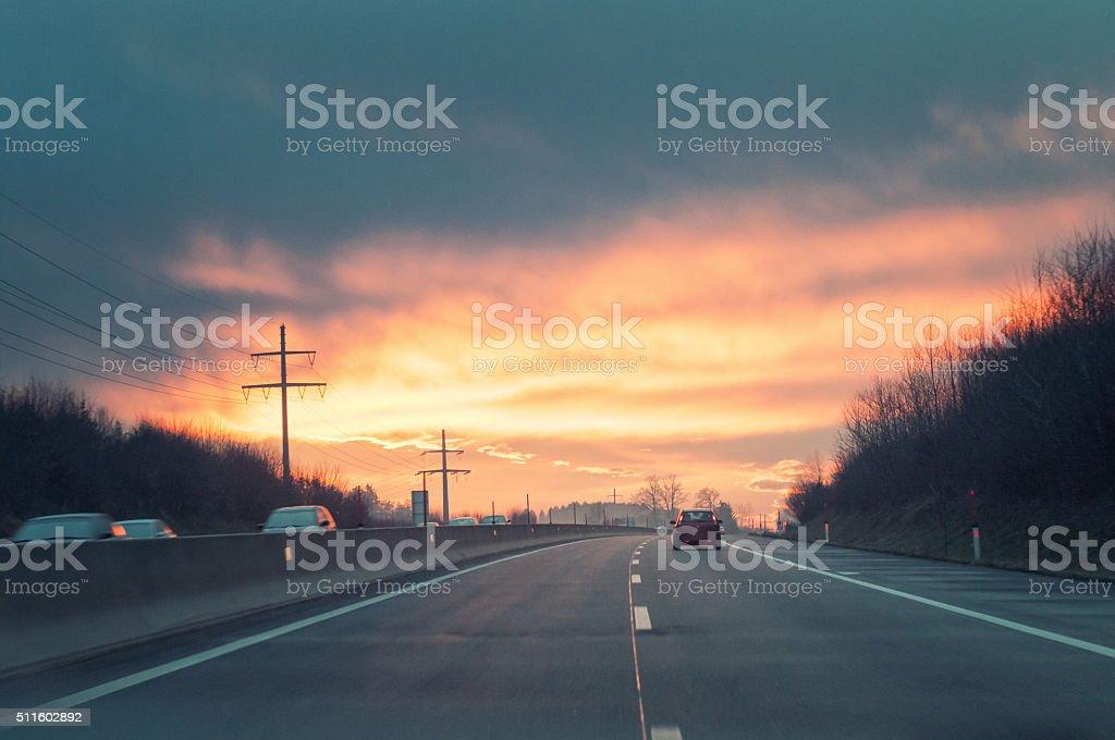 Driving thru highway at sunset. stock photo