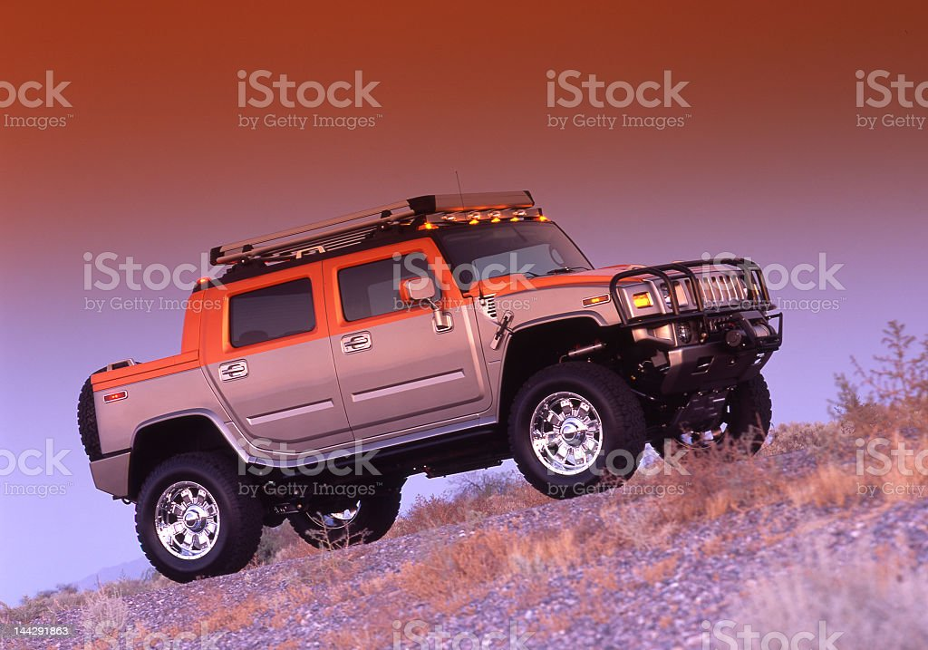 SUV driving up rugged hill terrain in low light stock photo