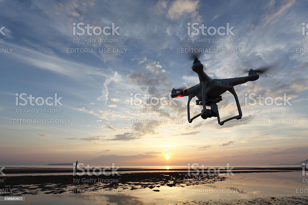 Drone flying against a sunset sky stock photo
