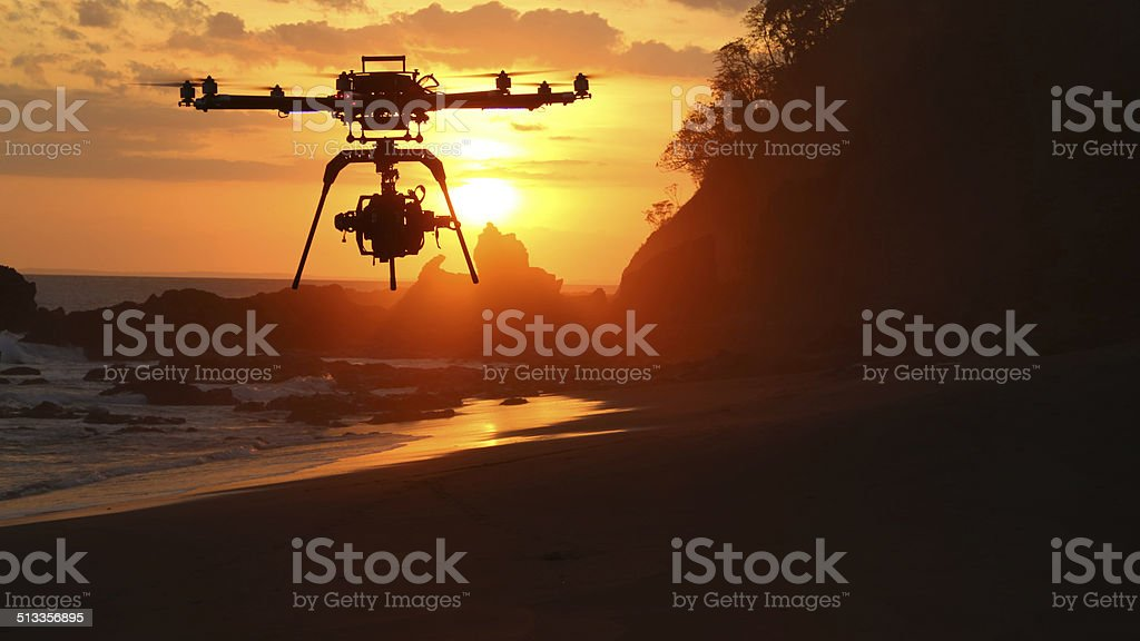 Drone UAV at sunset over beach stock photo