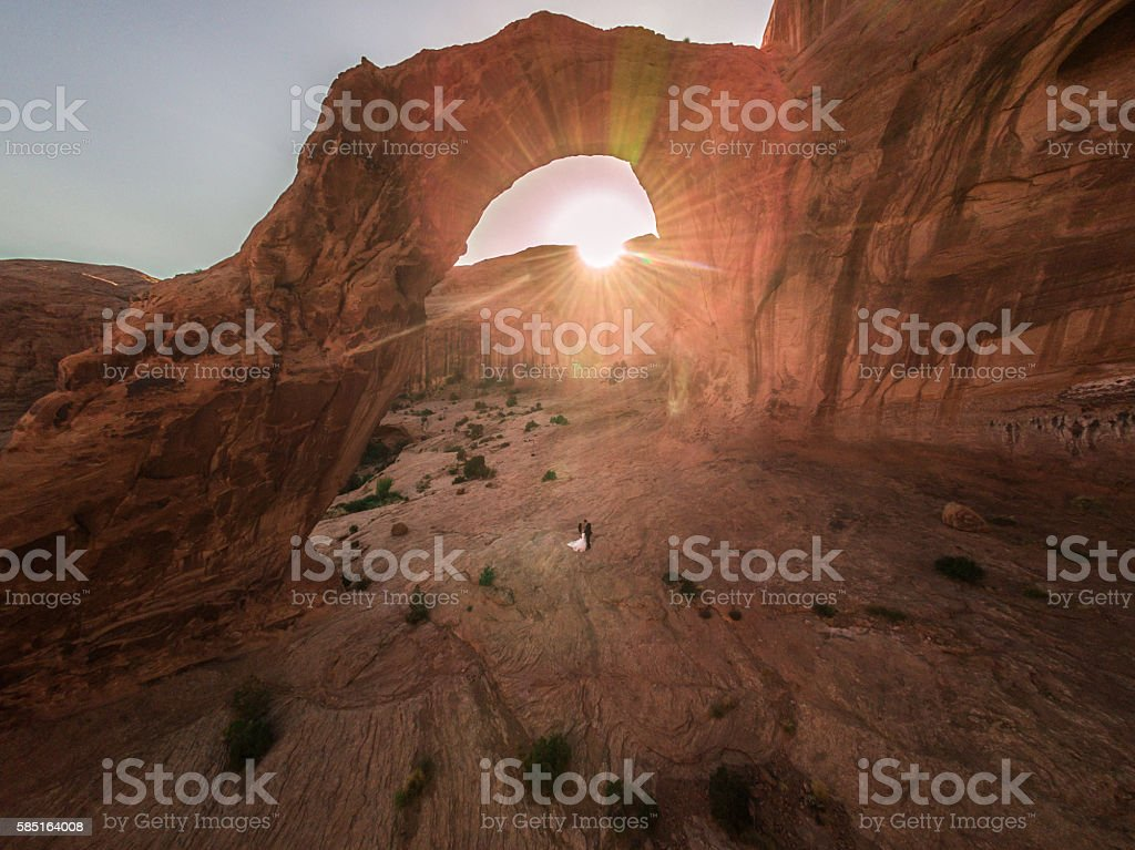 Drone/Aerial Photo.  Bride & Groom under Utah Desert arch stock photo