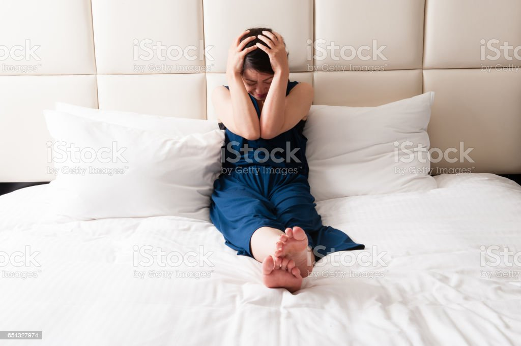 Drooping sitting on bed Japanese women stock photo