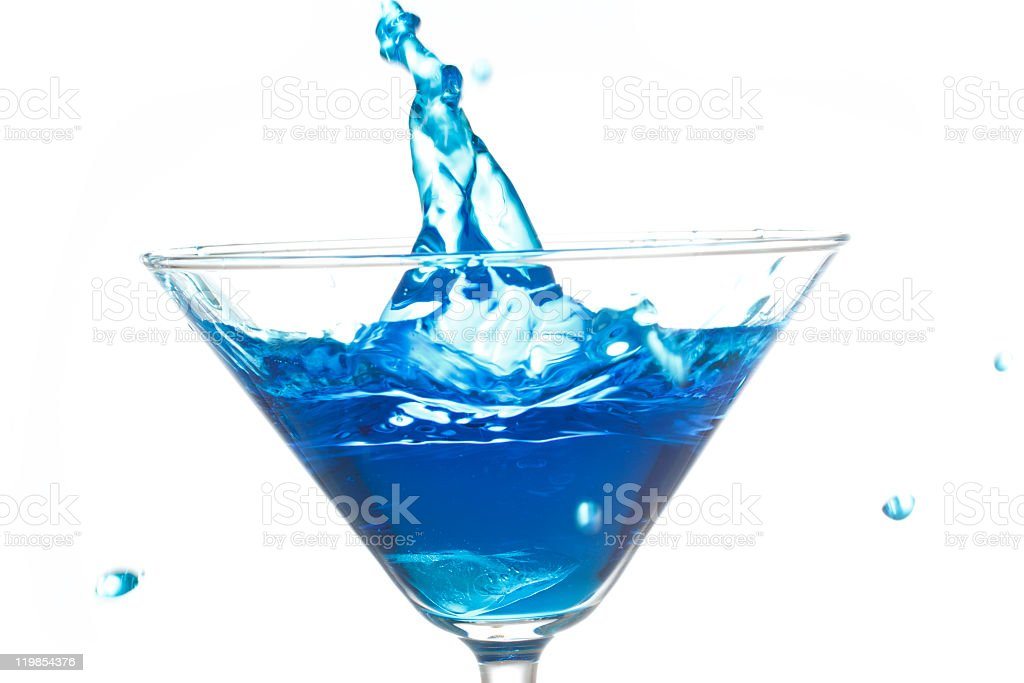 Drop of Blue Beverage Splasing into a Cocktail Glass stock photo