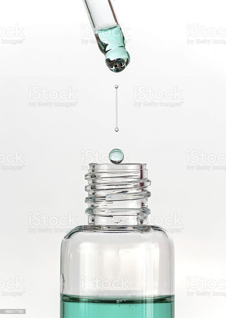 Drop of mouthwash dripped and falling into a clear bottle stock photo
