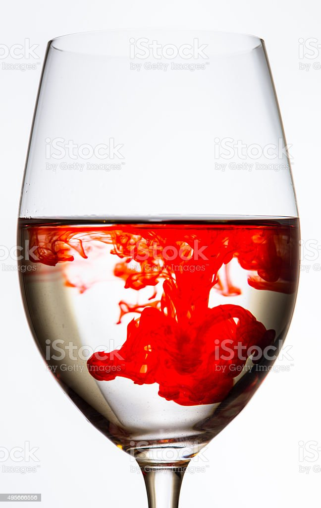 drop of red color spreading in wine glass stock photo