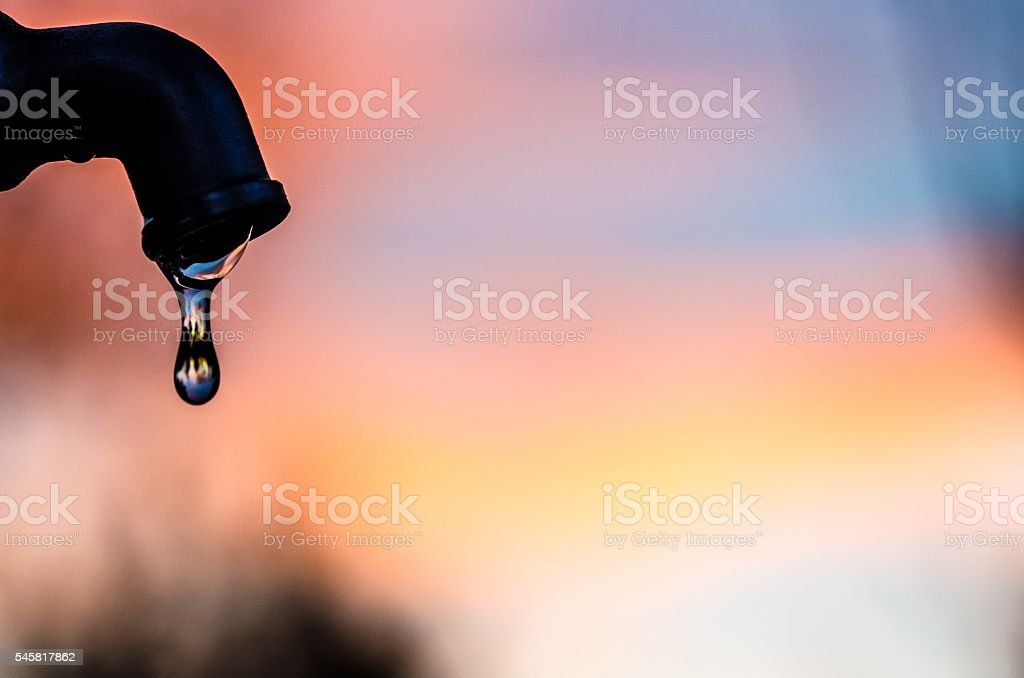 Drop of water coming out of a metal tap stock photo