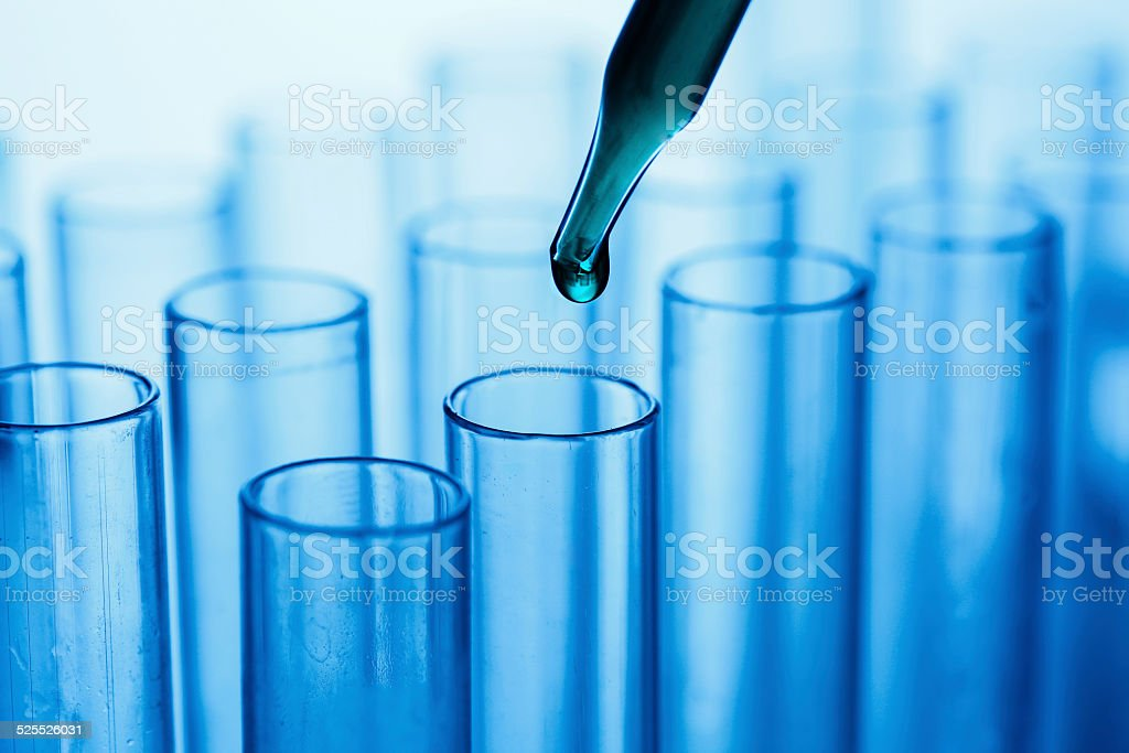 Droplet falling from pipette into test tube stock photo