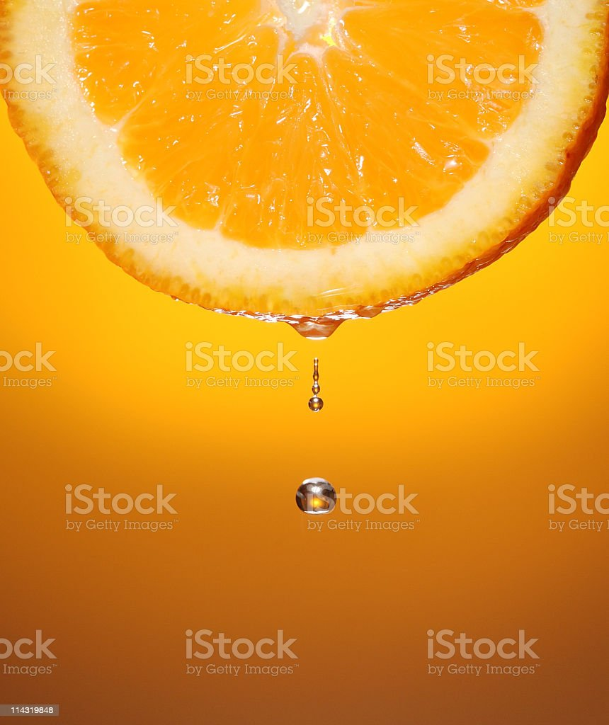 Droplet of orange juice dripping from a slice of orange stock photo
