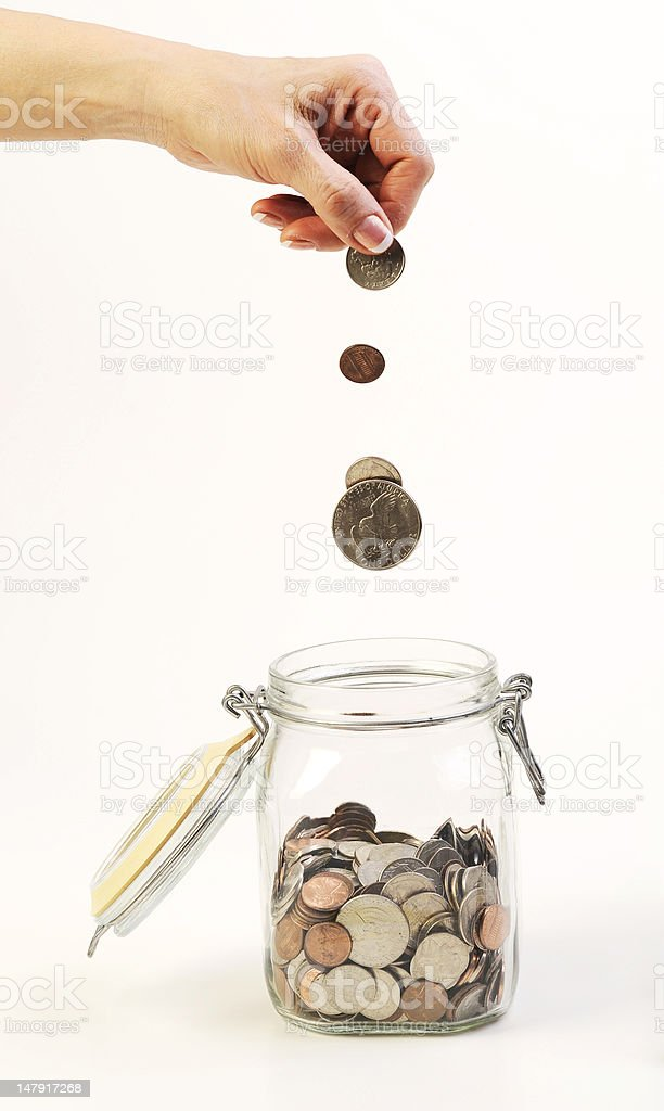 dropping coins into the glass jar royalty-free stock photo