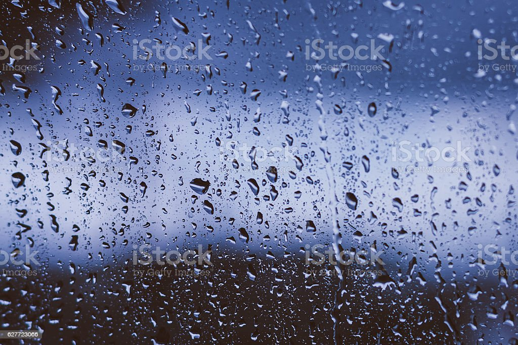 Drops Of Rain Water On Glass Background. Moody Toned Photo stock photo
