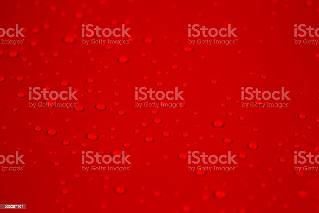 Drops of water on red background stock photo