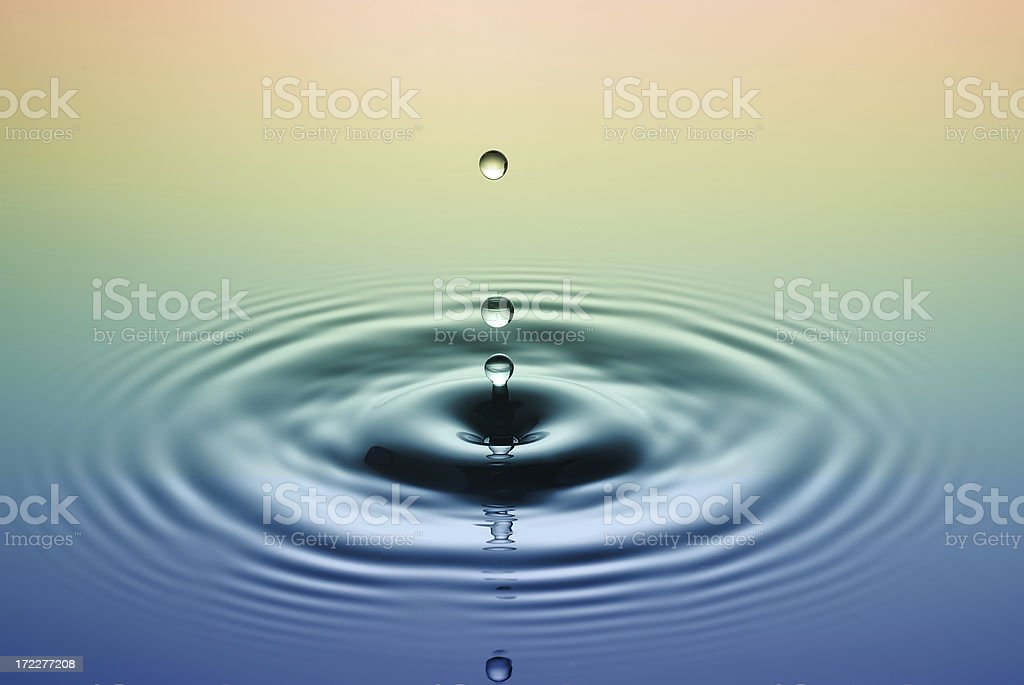 Drops of water rippling in blue and yellow stock photo