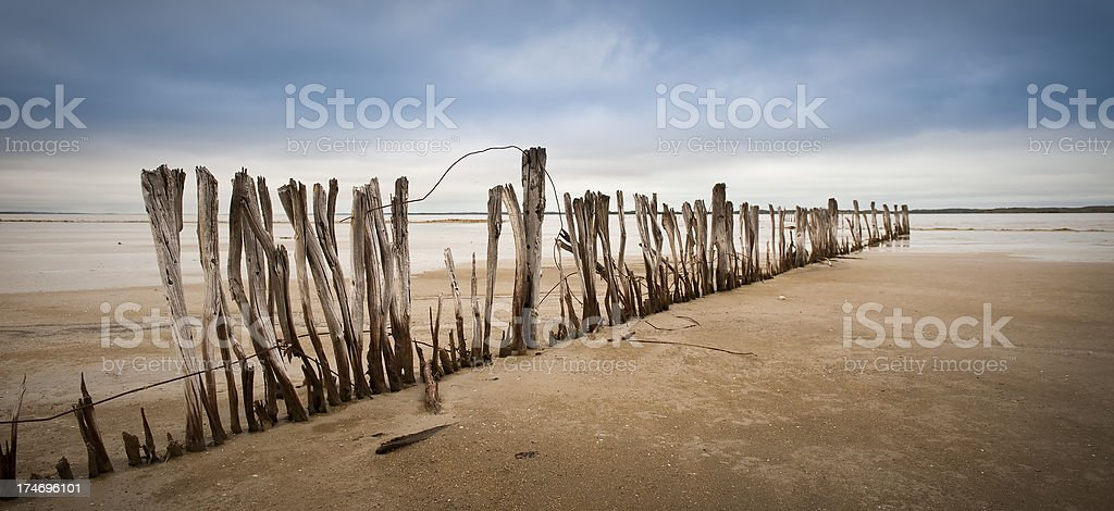 Drought dried lake wooden fence in disrepair stock photo