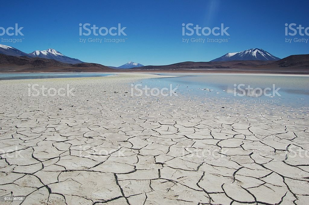 Drought Dry Lake Cracked Surrounded By Mountains and Blue Sky stock photo