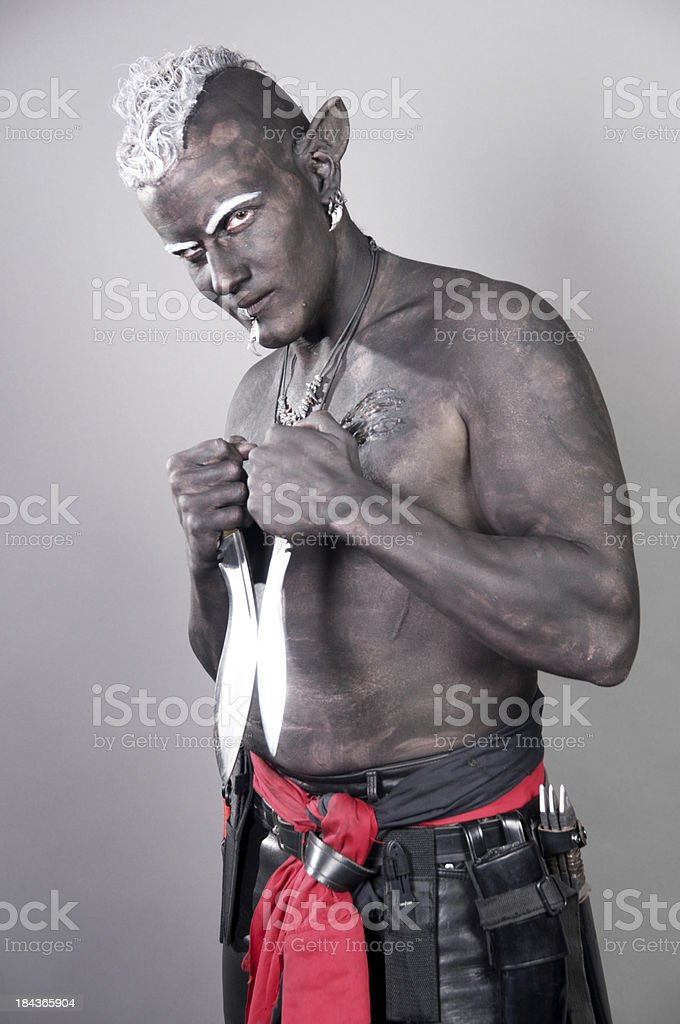 Drow Elf with blades smiling menacingly. royalty-free stock photo