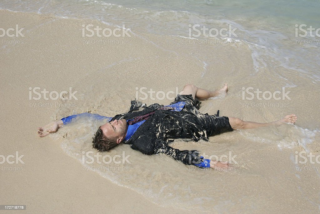 Drowned Castaway Businessman Lying in the Waves royalty-free stock photo