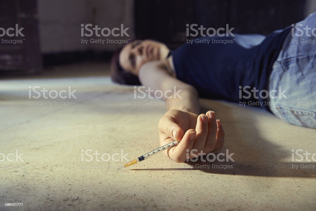 Drug abuse-young woman injecting heroin with syringe stock photo