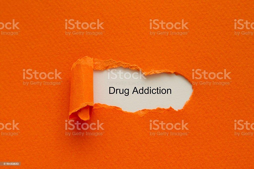 Drug Addiction written under torn paper. stock photo