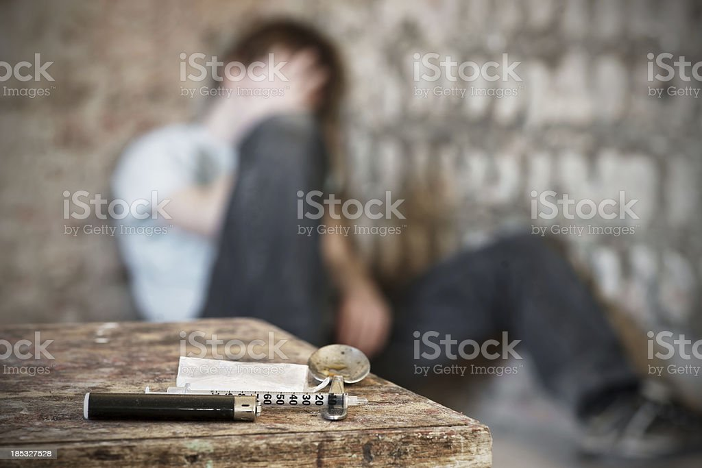 Drug paraphernalia with blurred addict behind stock photo