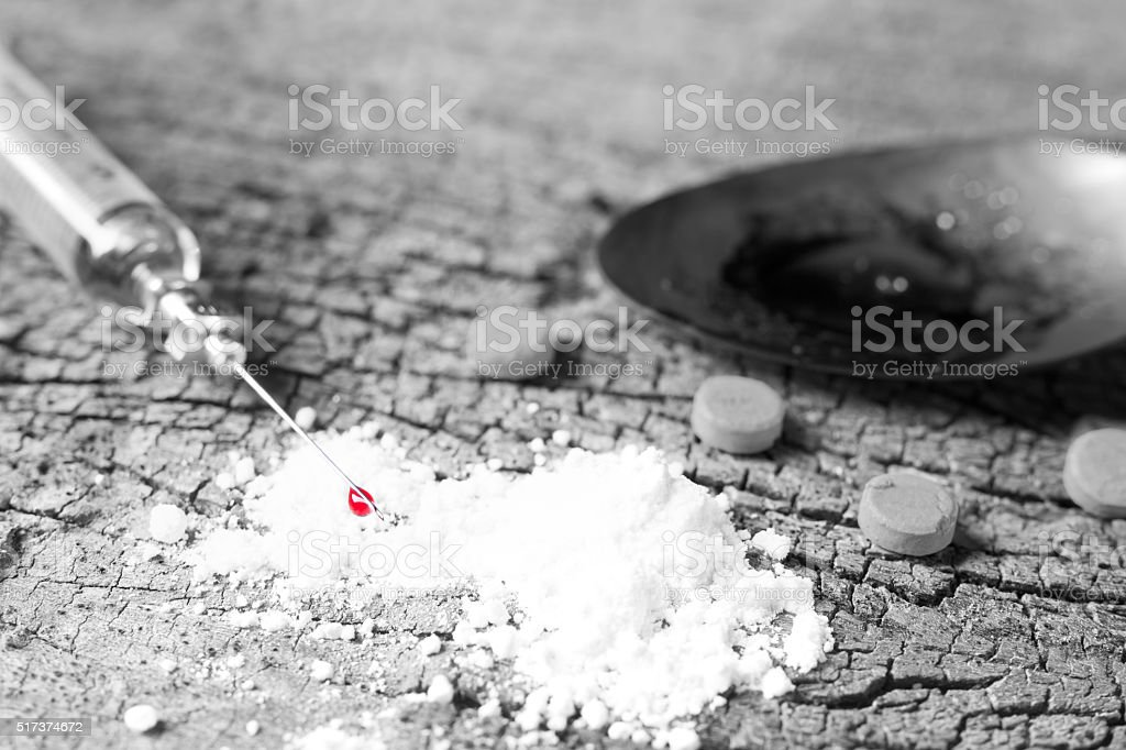 Drug syringe with blood, amphetamine tablets and cooked heroin i stock photo