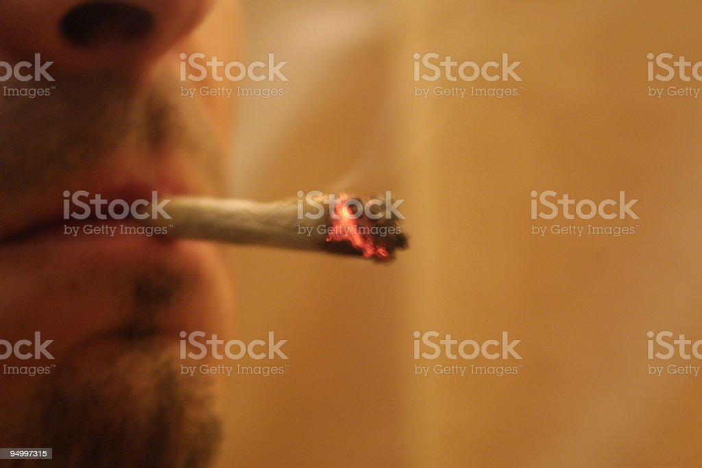 A drug user with a lit joint in mouth stock photo