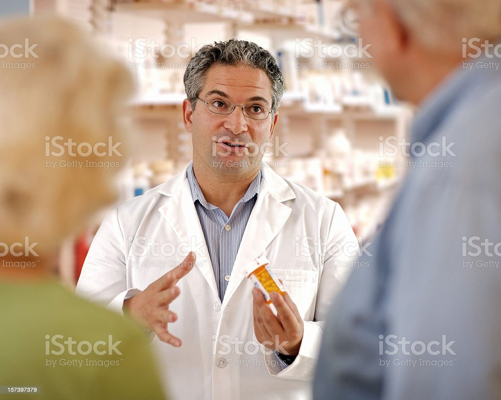 Druggist Consulting with Senior Couple royalty-free stock photo