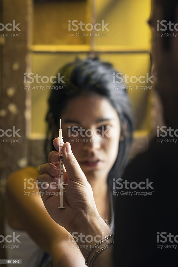 Drugs and people, man helping woman with heroin syringe royalty-free stock photo
