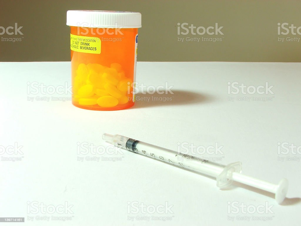 Drugs - Bottle of Pills and Syringe royalty-free stock photo