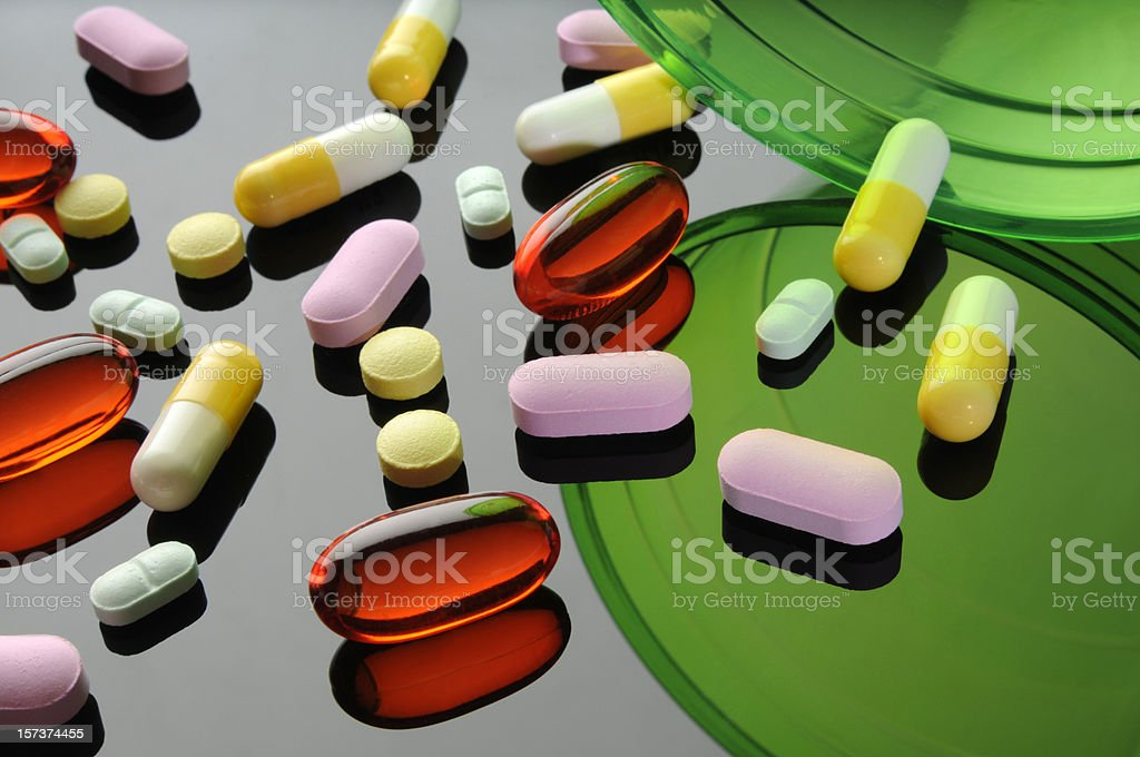 Drugs; Colorful Pills, Clear Capsules, Reflective Mirrored Surface, Red, Green royalty-free stock photo