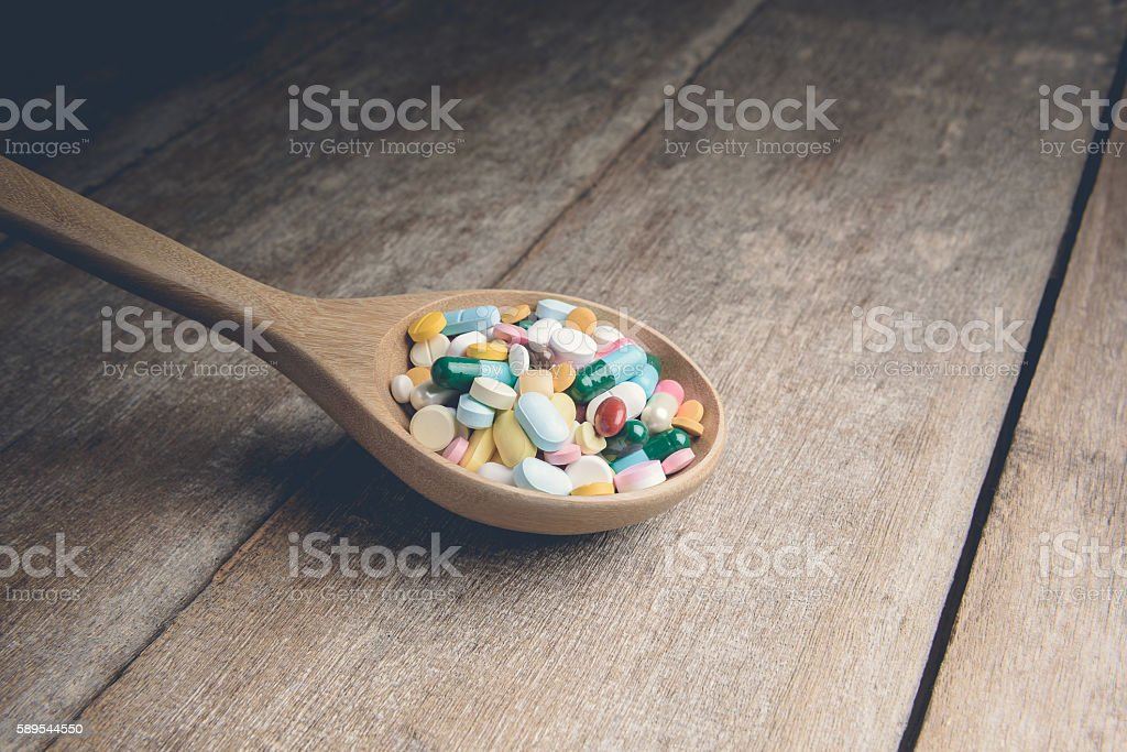 Drugs pill on wooden spoon for your treatment your health stock photo