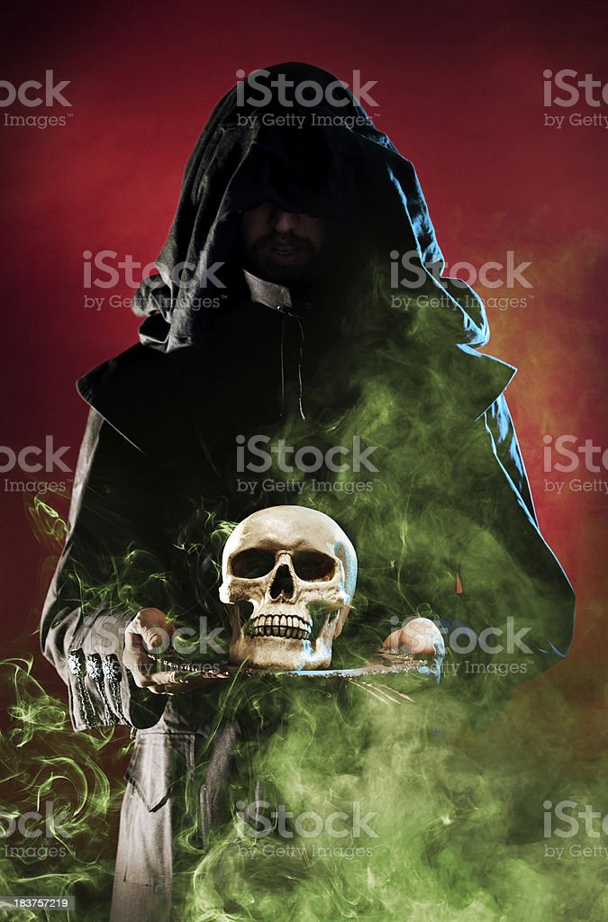 Druid witch in black holding skull on platter smoke occult stock photo