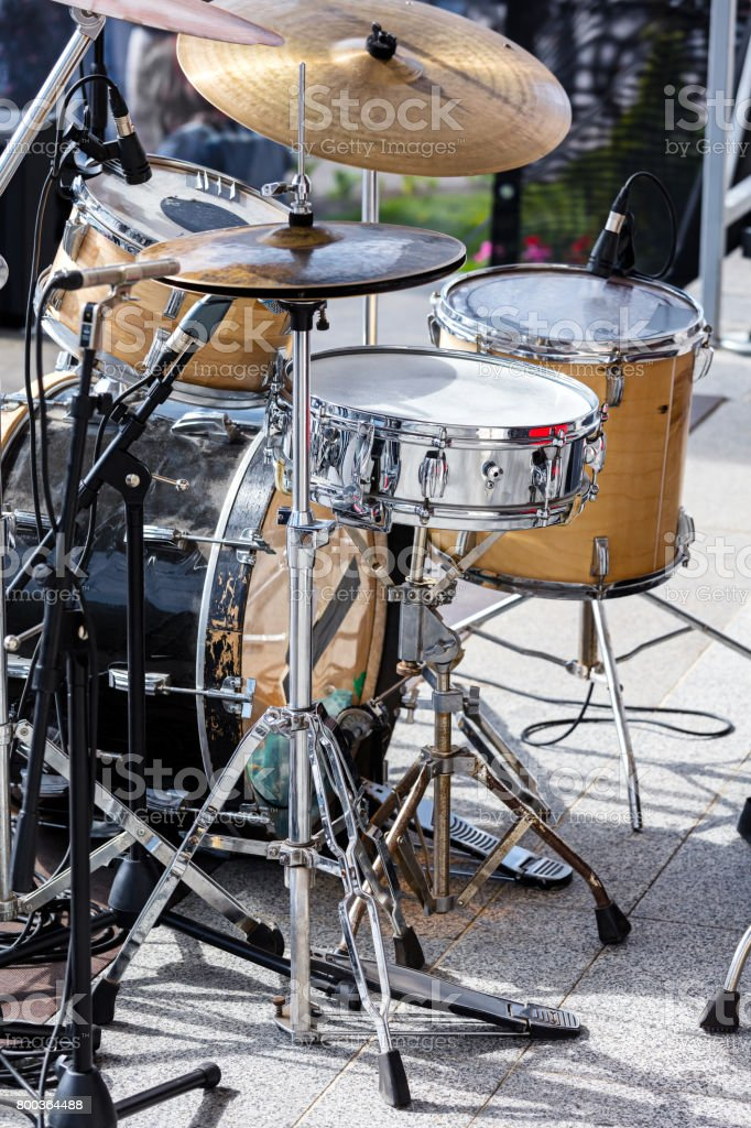 drum kit with microphones standing on outdoor stage stock photo