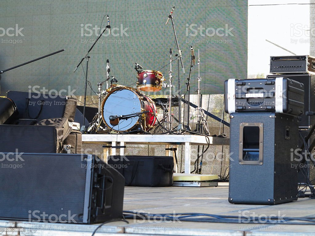 Drum set, microphones and speakers on stage stock photo