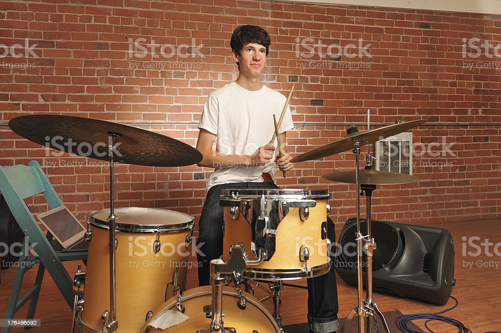 Drummer in a brick and wood studio jamming royalty-free stock photo