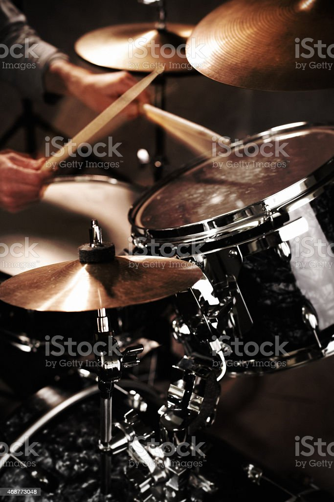 Drummer playing drumset with motion blurred sticks stock photo