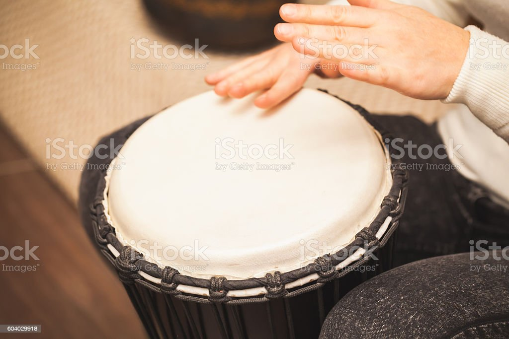 Drummer plays on small African drum stock photo