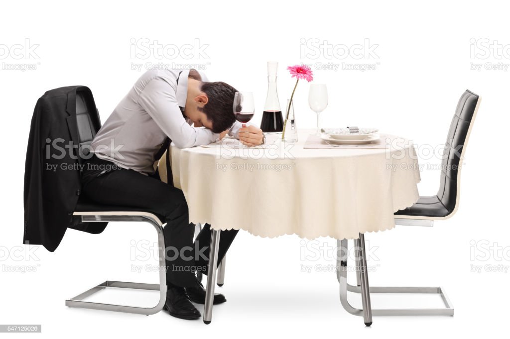 Drunk and lonely guy sitting at a table stock photo