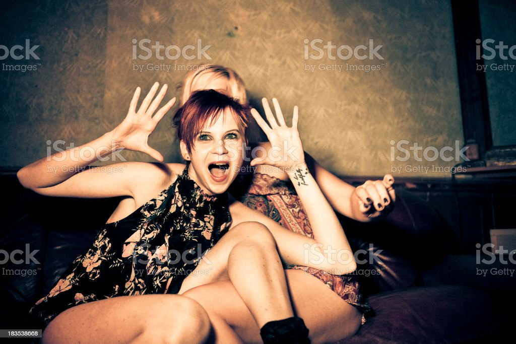Drunk best friends making faces on a sofa stock photo