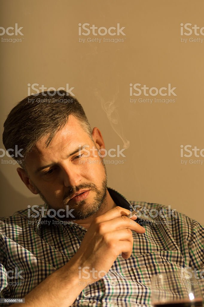 Drunk businessman smoking a cigarette stock photo