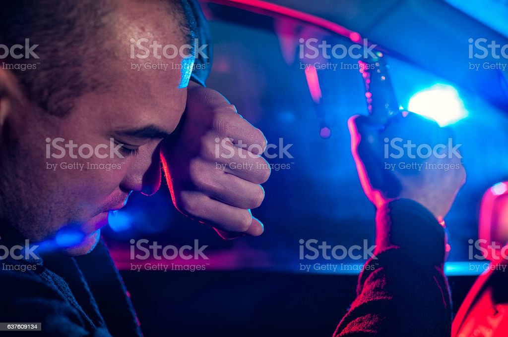 Drunk driver covering face from police car light stock photo