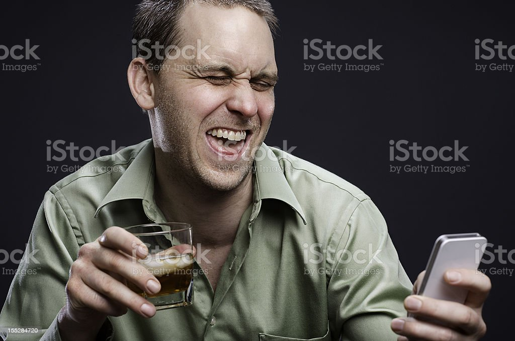 A drunk man drinking and texting stock photo