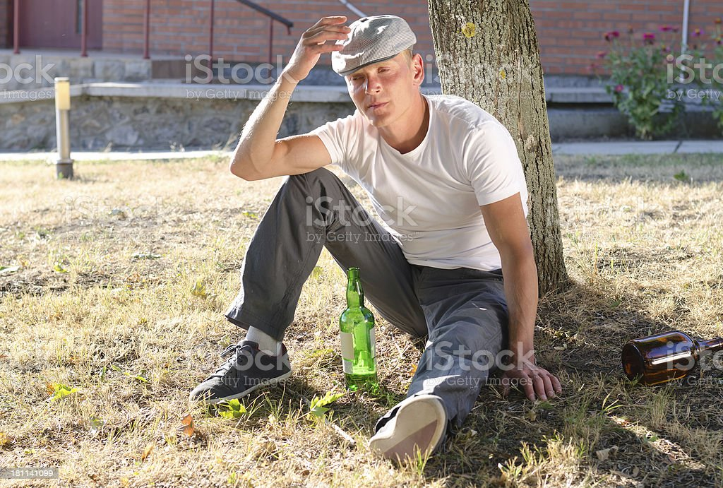 Drunk man sitting at the base of a tree stock photo