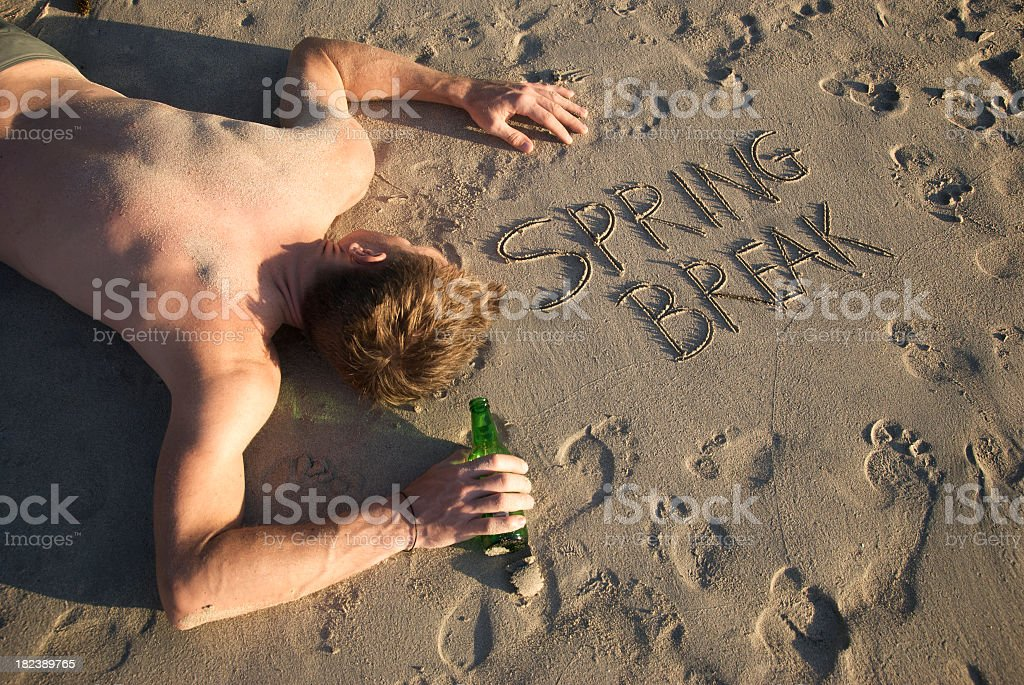 Drunk Spring Break Casualty with Beer Bottle Lying on Beach royalty-free stock photo