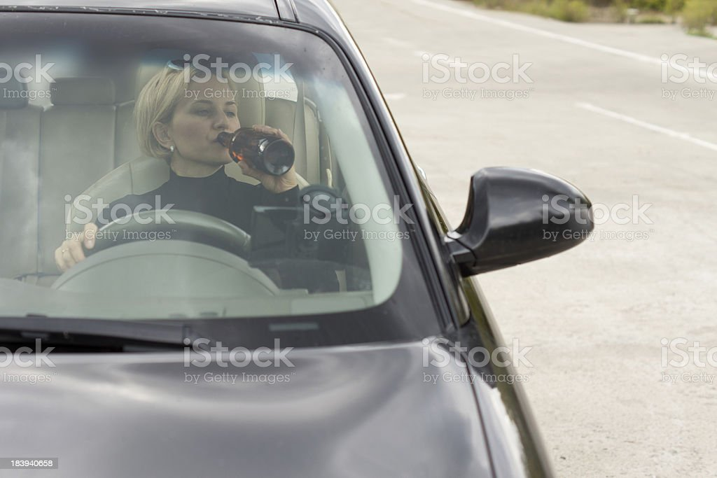 Drunk woman driving and drinking royalty-free stock photo