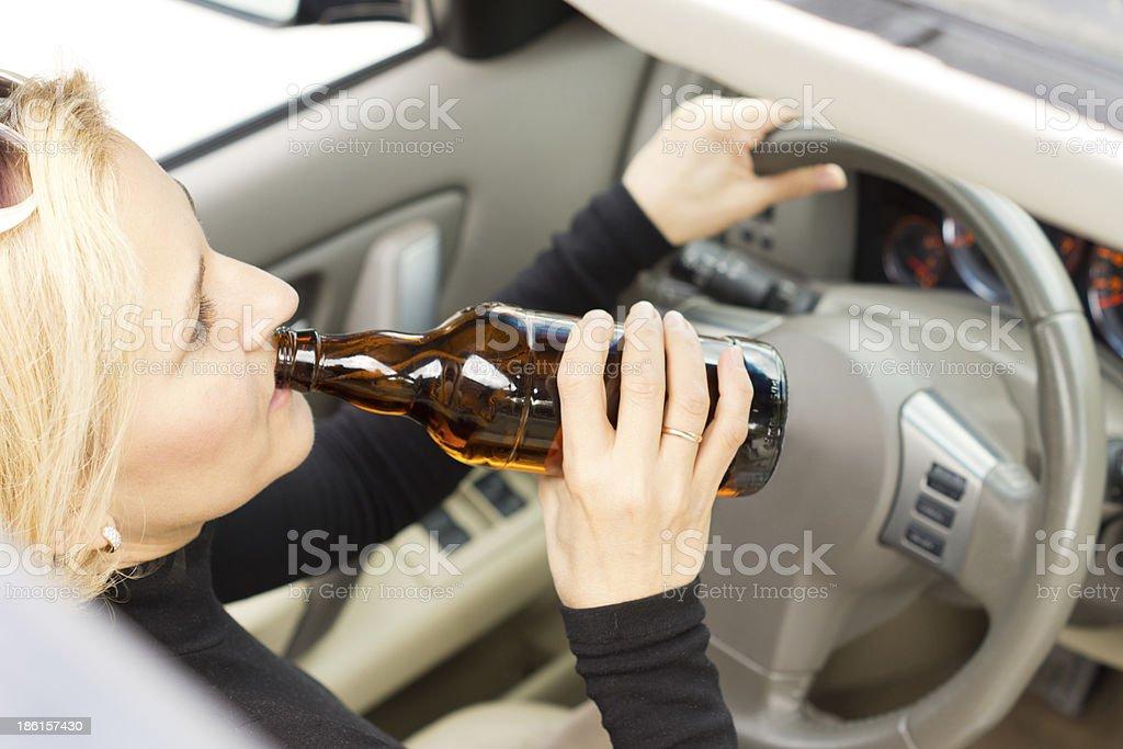 Drunk woman imbibing as she drives royalty-free stock photo