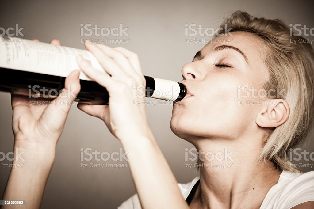 Drunk woman with bottle of wine stock photo