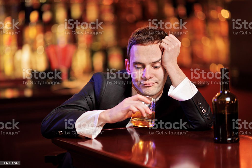 A drunk young man drinking and slouching on the bar stock photo